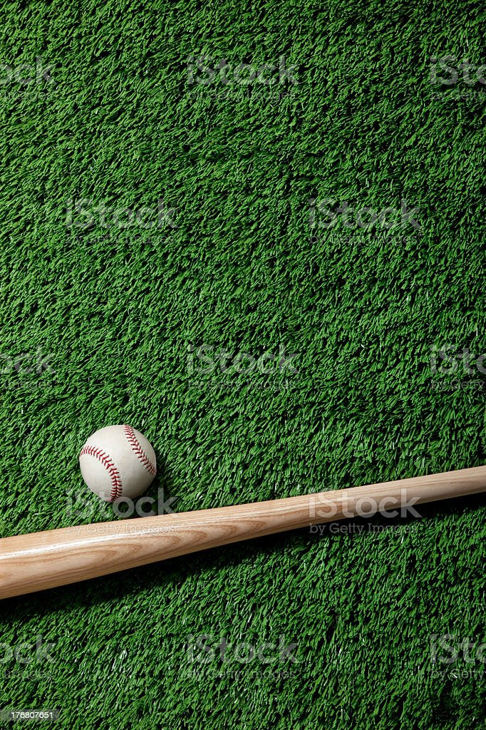 A baseball and wooden bat on artificial green grass stock photo