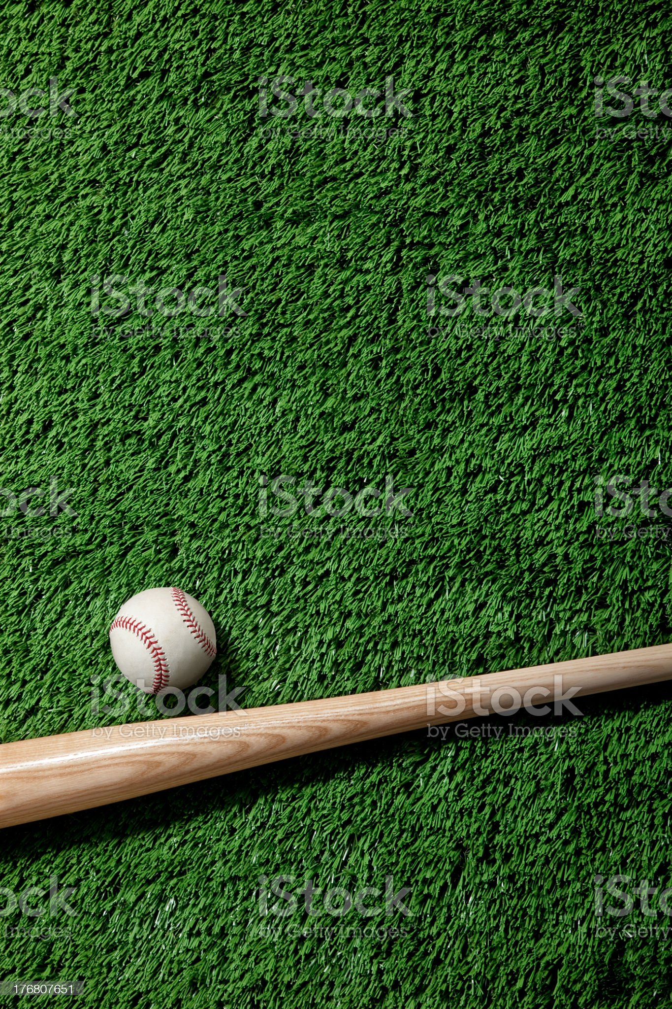 A baseball and wooden bat on artificial green grass royalty-free stock photo