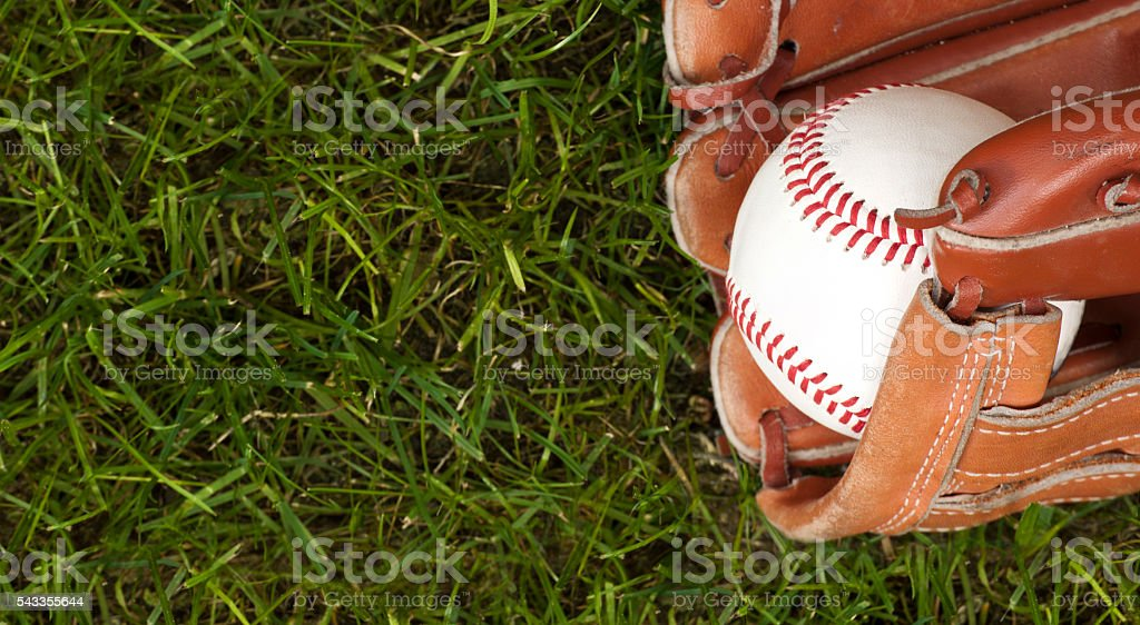 Baseball ball and glove on green grass stock photo