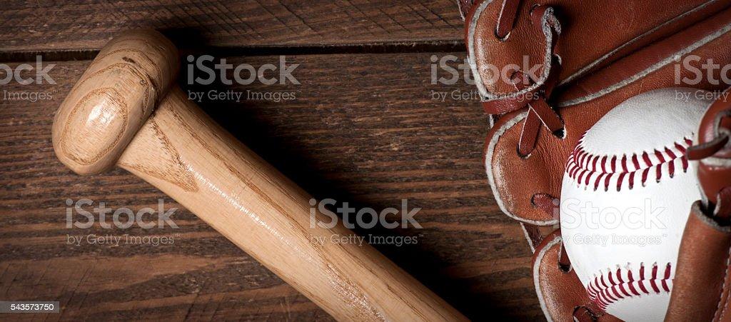 Photo of an Baseball ball, glove and bat on wooden table. Studio shot