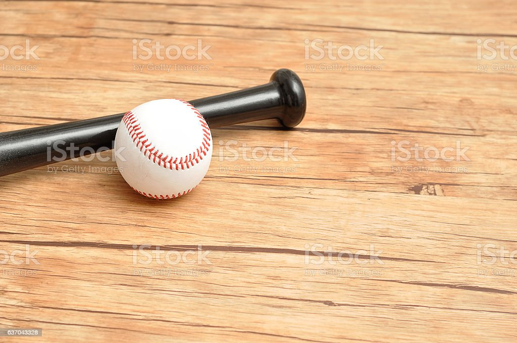 A baseball bat and ball isolated on a wooden background