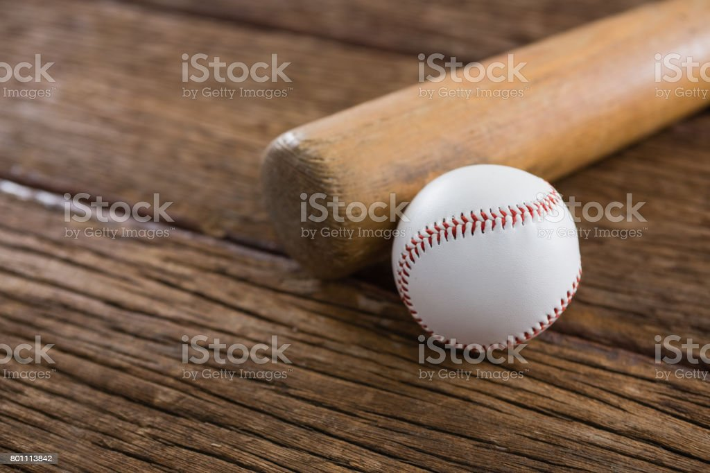 Close-up of baseball bat and ball on wooden table