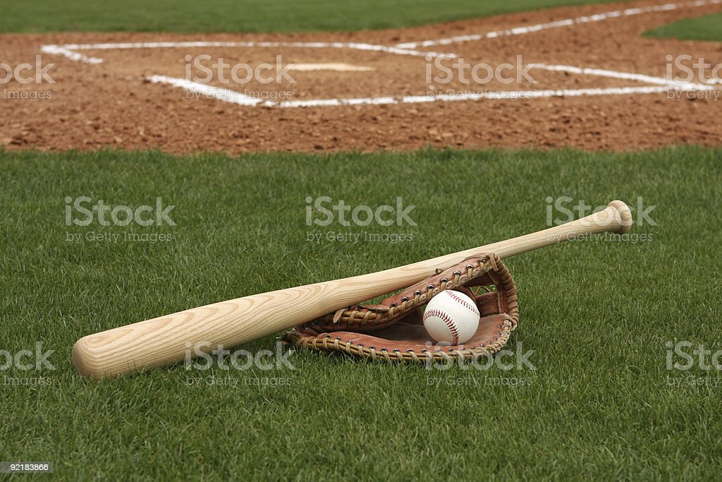 Baseball, bat, and glove on field in front of home plate royalty-free stock photo
