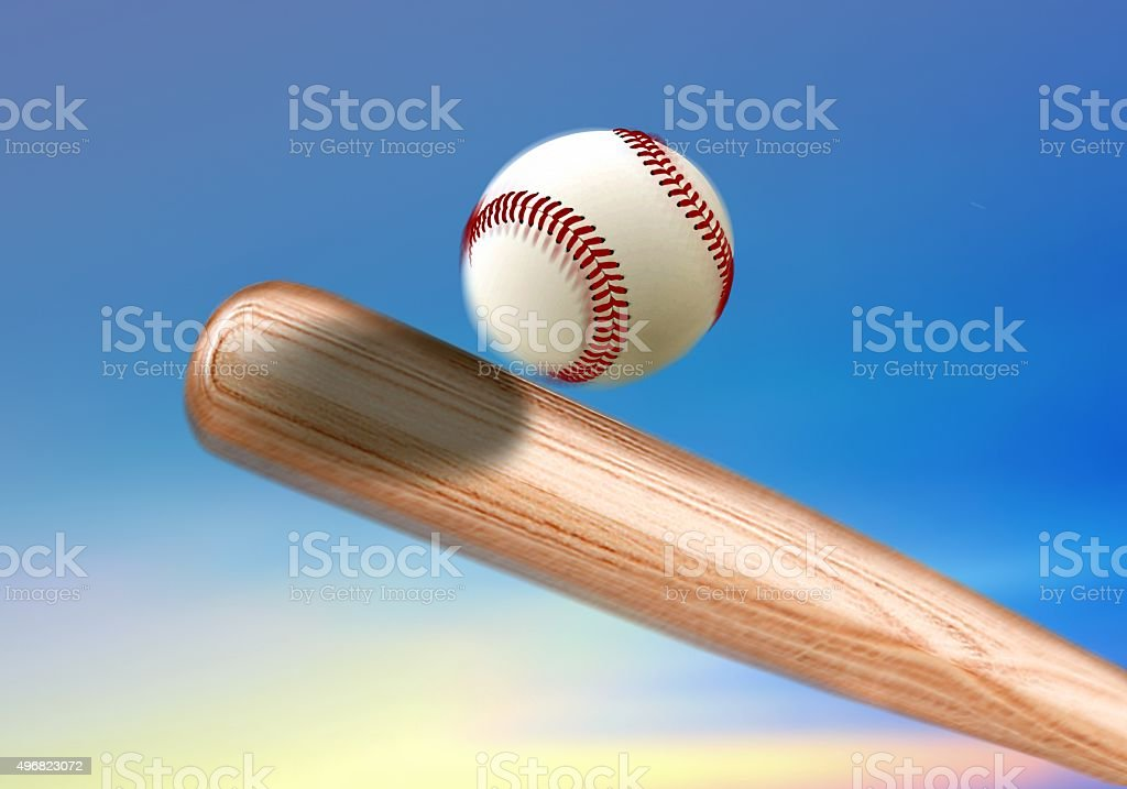Baseball bat hitting ball under blue sky stock photo