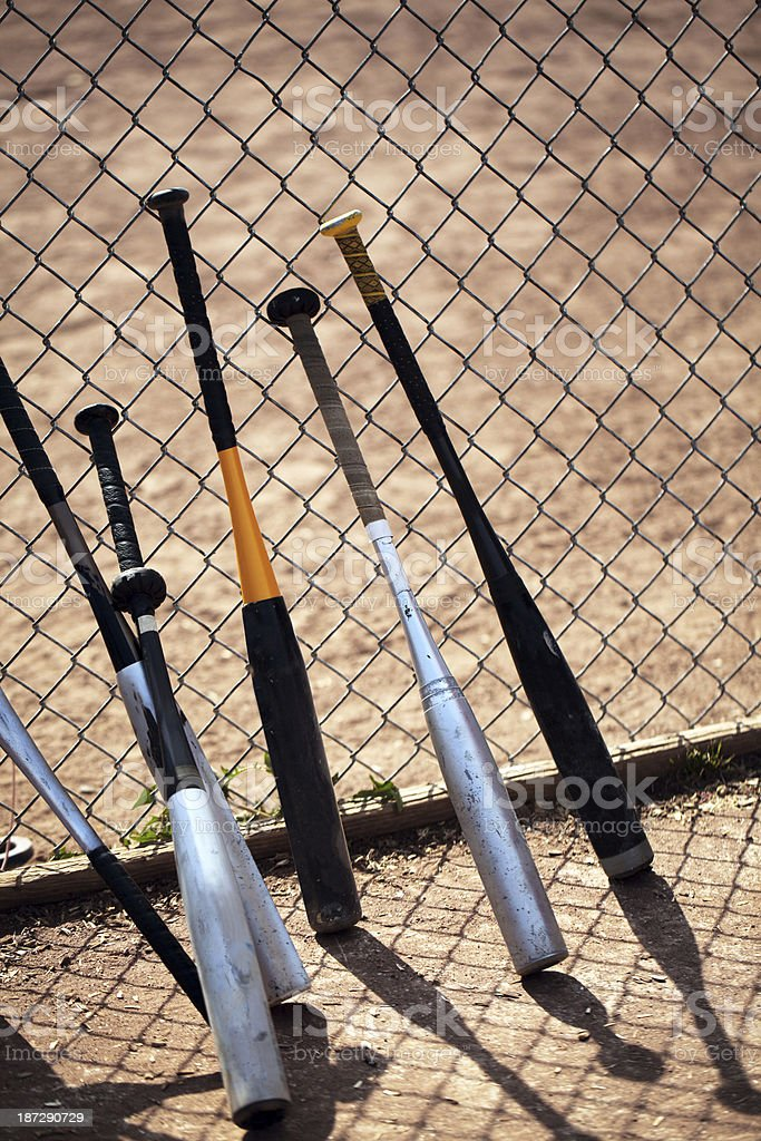 Baseball bats lean against chain link fence during game. stock photo