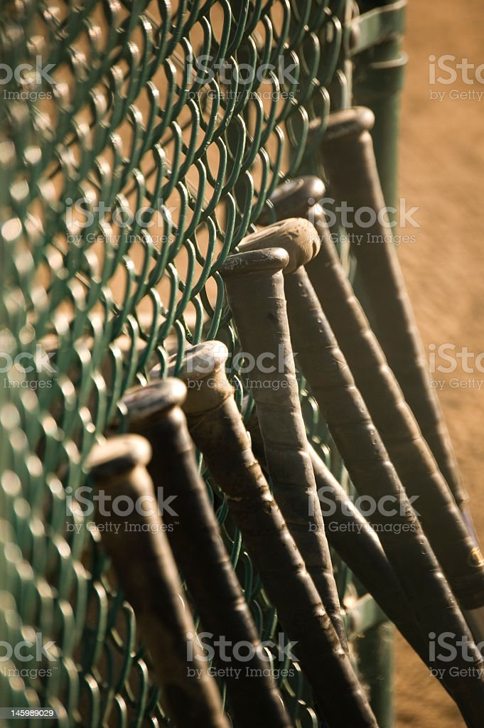 Baseball bats lined up against a fence stock photo