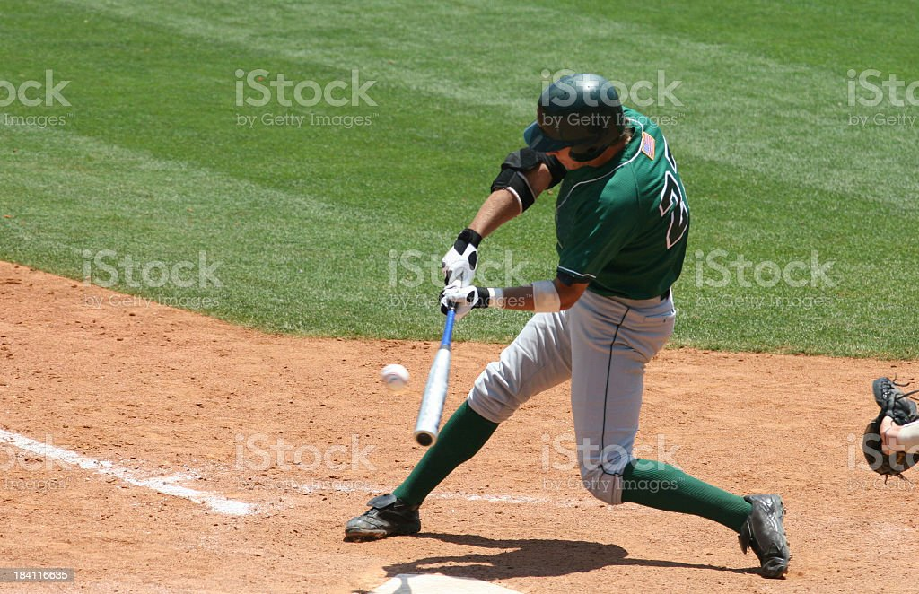 Baseball batter in green uniform hitting ball royalty-free stock photo