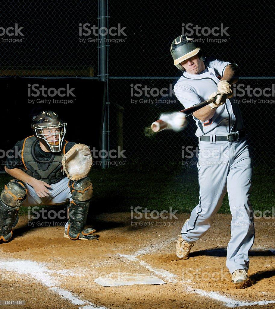 Baseball batter smashes ball, it's headed for the fenses! stock photo