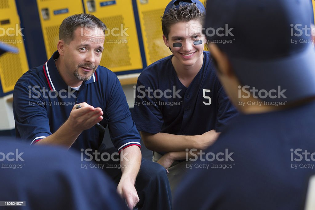 Baseball coach motivating his players in locker room before game stock photo