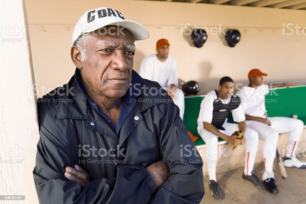Baseball Coach Watching From Dugout stock photo