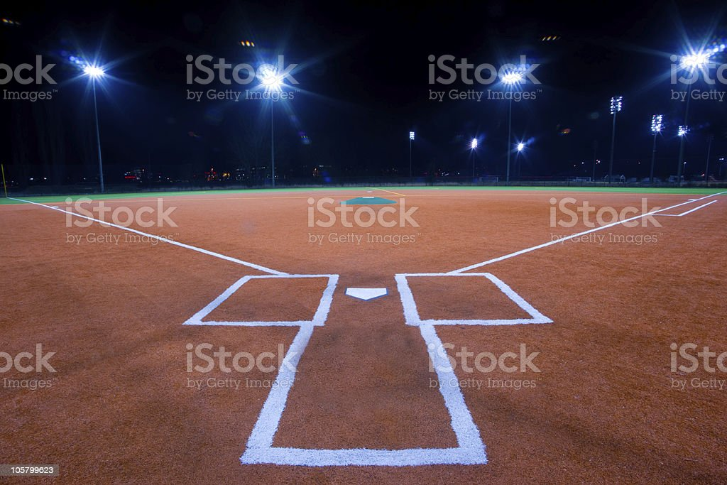A baseball diamond view from behind home plate at night stock photo