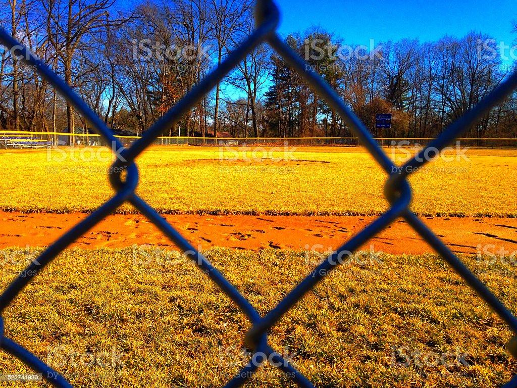 Baseball field seen through fence in dugout stock photo