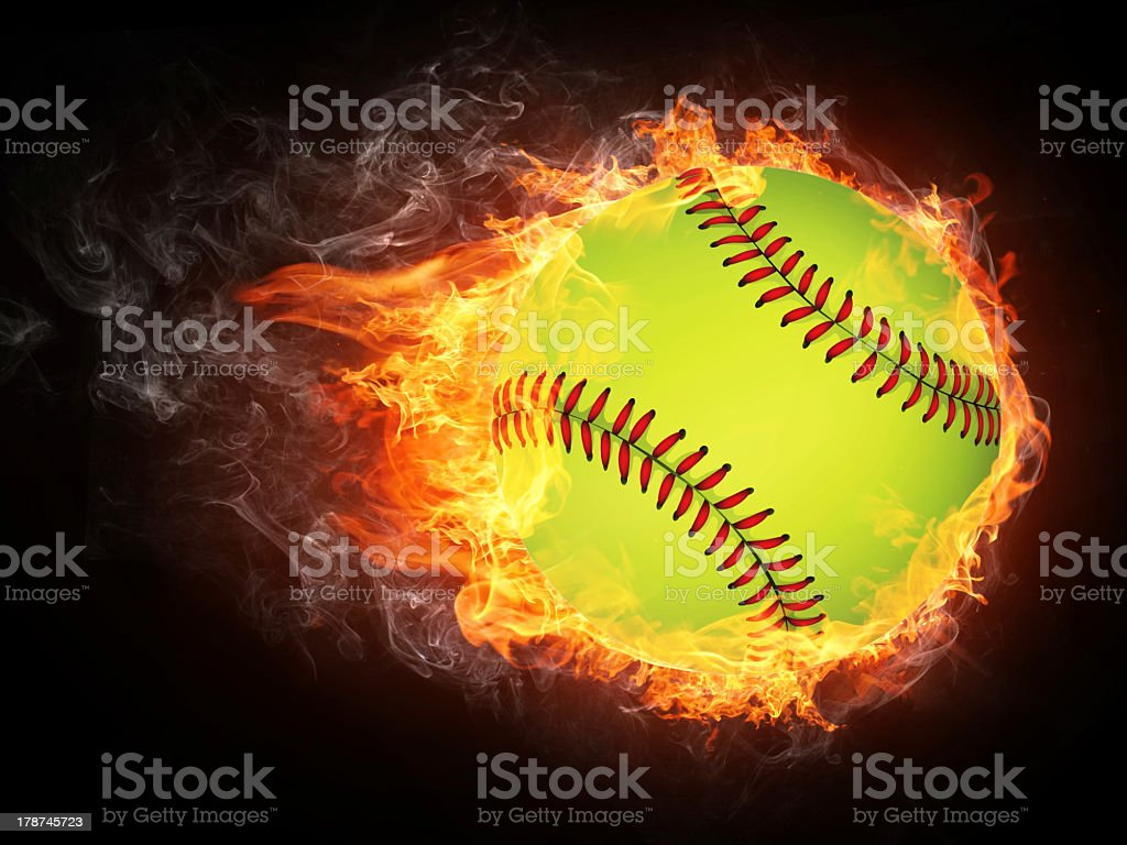 Baseball flies through black background engulfed in flames stock photo
