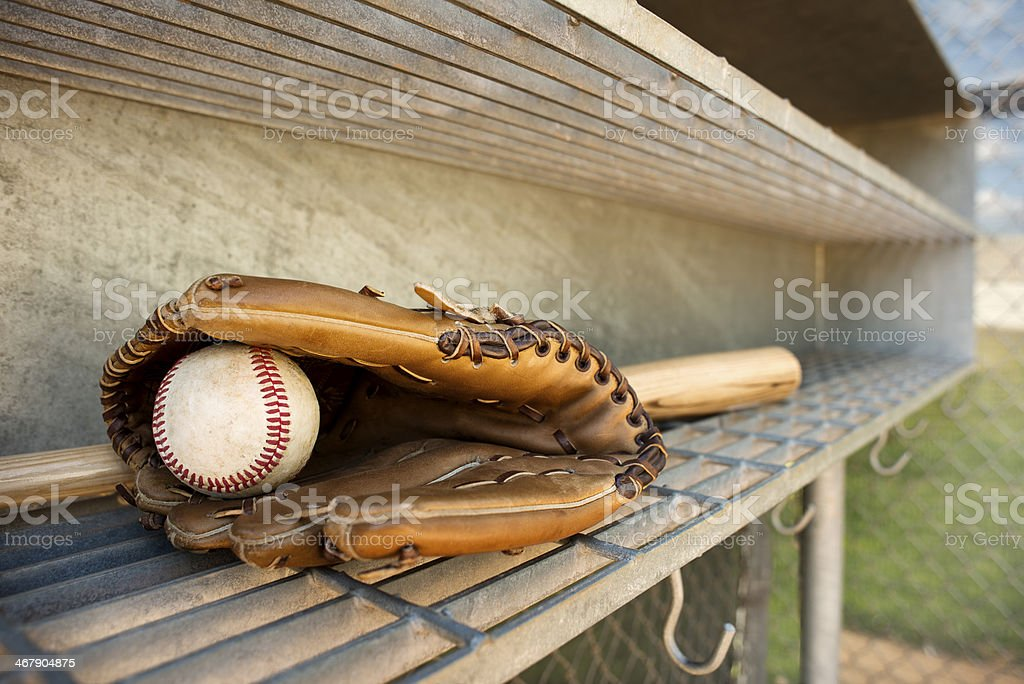 Baseball, glove and bat in dugout stock photo