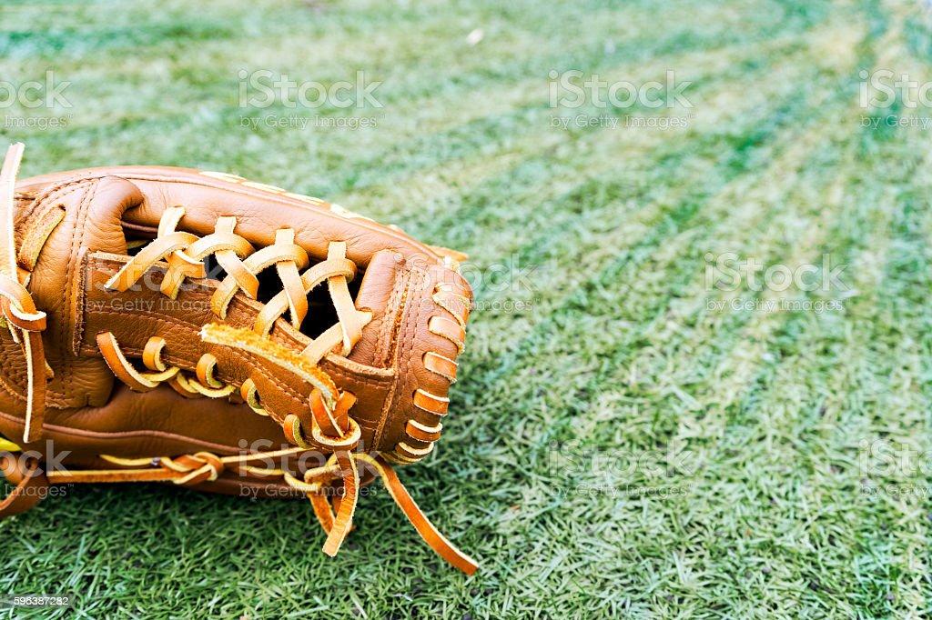 Baseball glove on grass in stadium, with golden sun ray stock photo