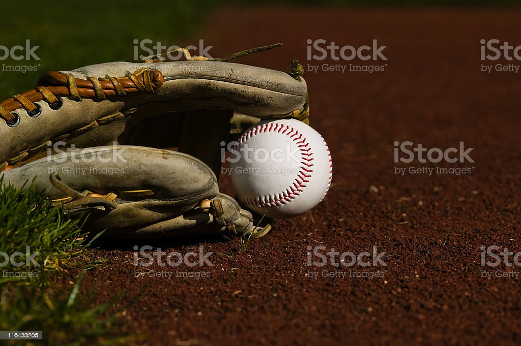Baseball in a glove sitting on the grass and dirt of a diamond