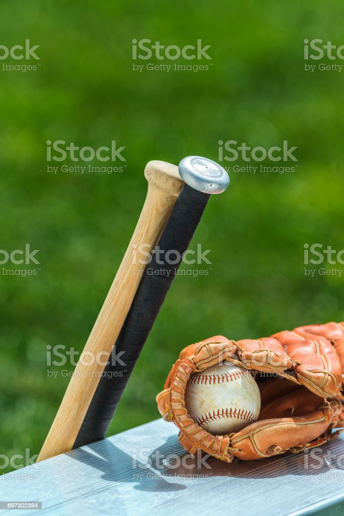 Baseball in glove with an aluminum and wooden bats on park bench stock photo