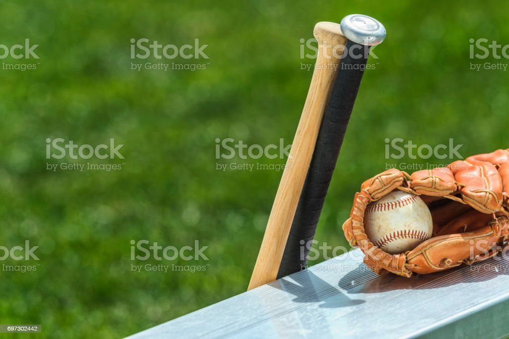A baseball in a brown leather baseball glove sitting on an aluminum...