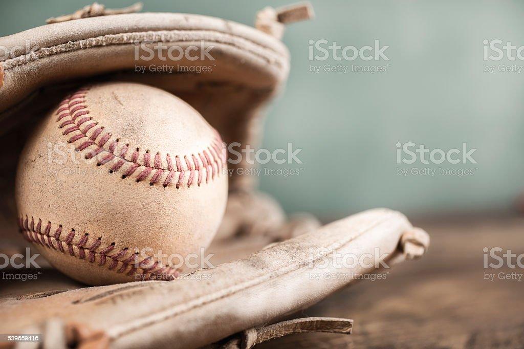 A baseball inside a glove on a wooden school desk. A green chalkboard...
