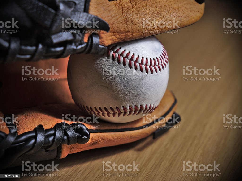 Close-up of a Baseball leather glove with ball on a wooden surface....
