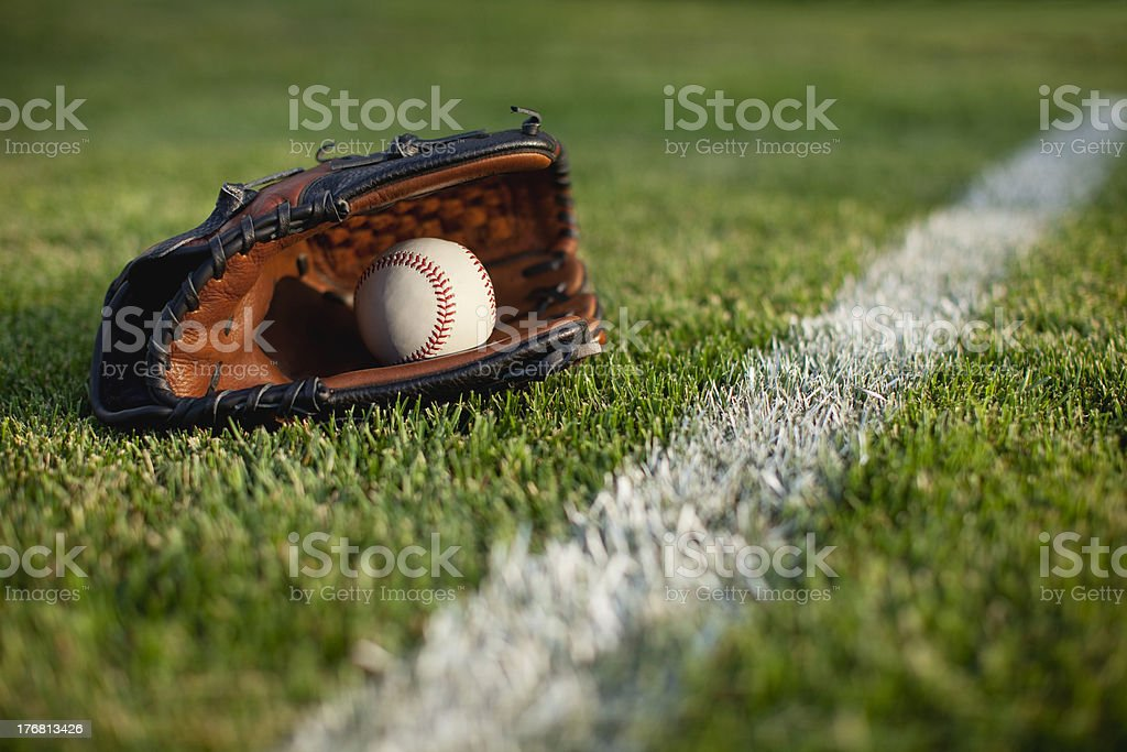 Baseball mitt and ball in grass with selective focus stock photo
