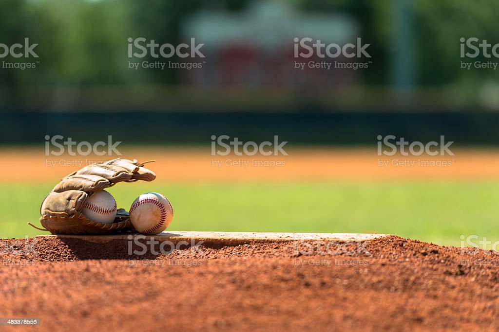 Baseball mitt and baseballs on pitchers mound stock photo