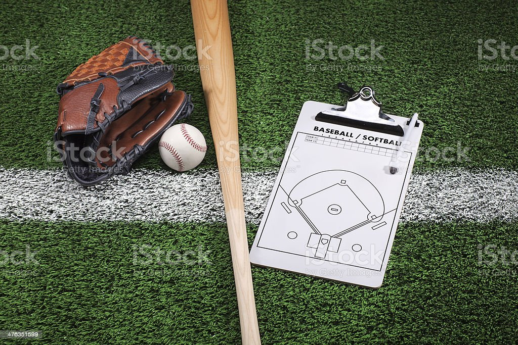 Baseball mitt, bat and clipboard on grass with stripe stock photo