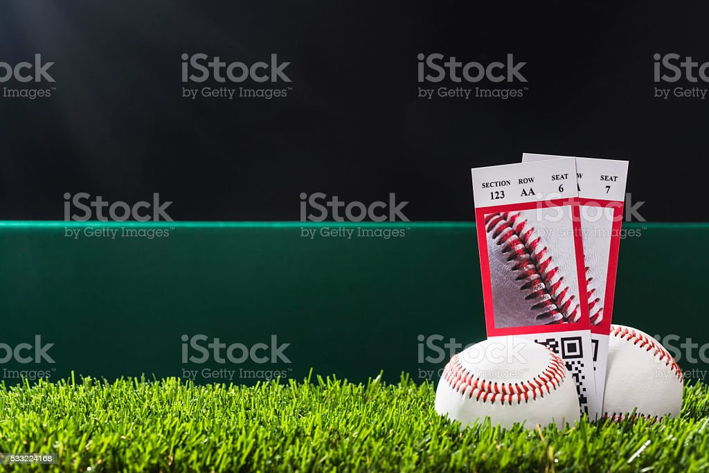 Baseball night game ticket stubs in outfield grass with ball stock photo