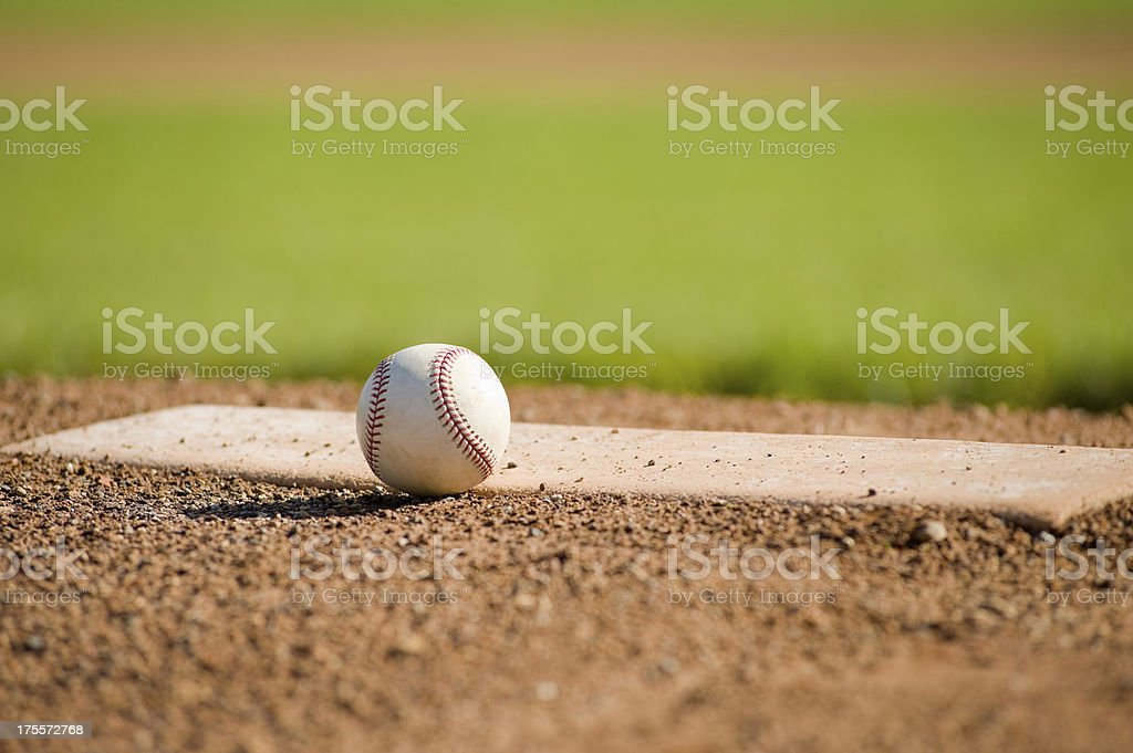 Baseball on a mound with the field in the background stock photo