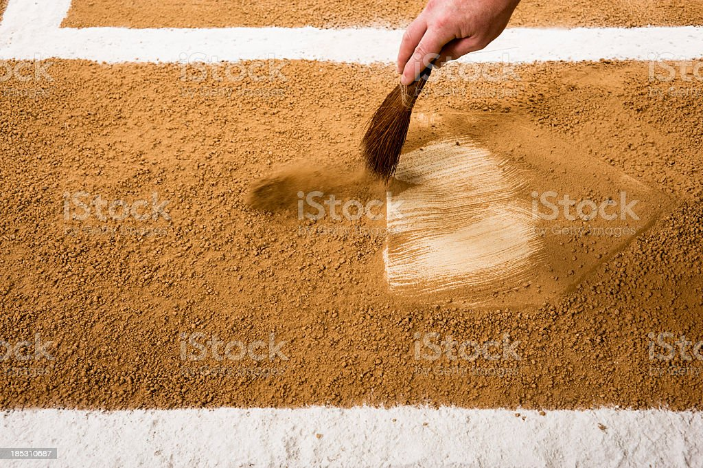Baseball or softball umpire cleaning home plate. Play Ball!!! stock photo