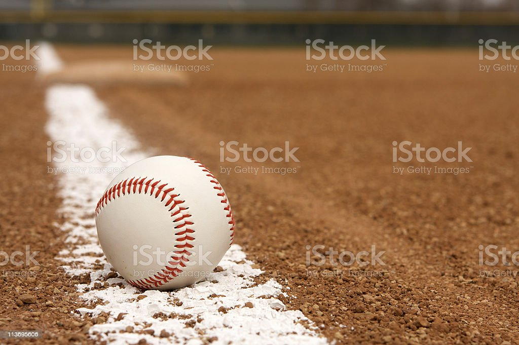 Baseball over chalk line of stadium field stock photo
