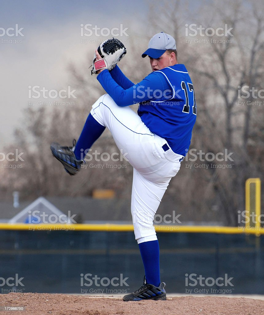 A baseball pitcher in blue getting ready to throw royalty-free stock photo