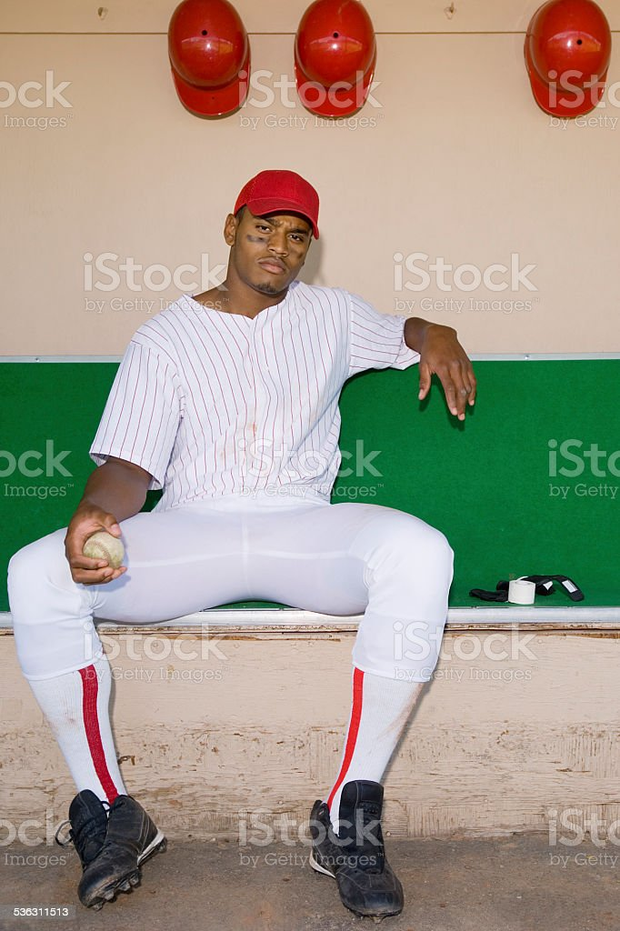 Baseball Pitcher Sitting in Dugout stock photo