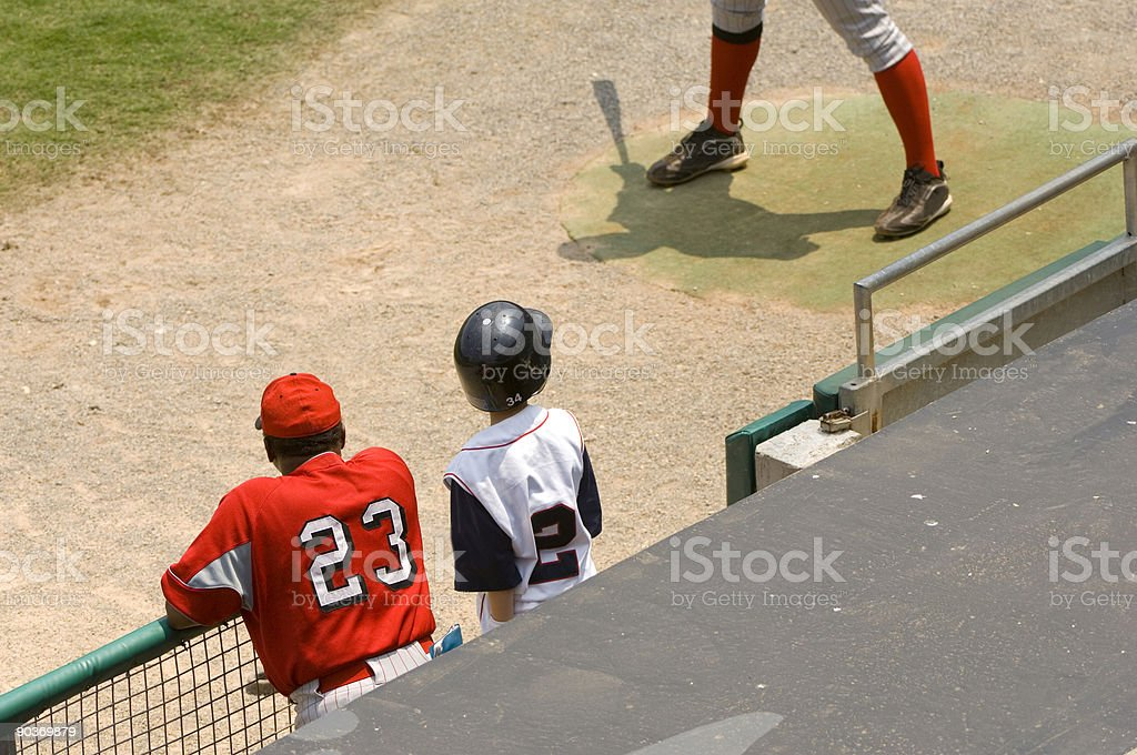 Baseball Player and Baseball Coach standing in dugout at a Baseball Game stock photo