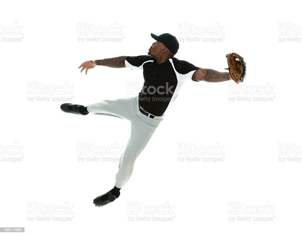 Baseball player jumping and fielding stock photo