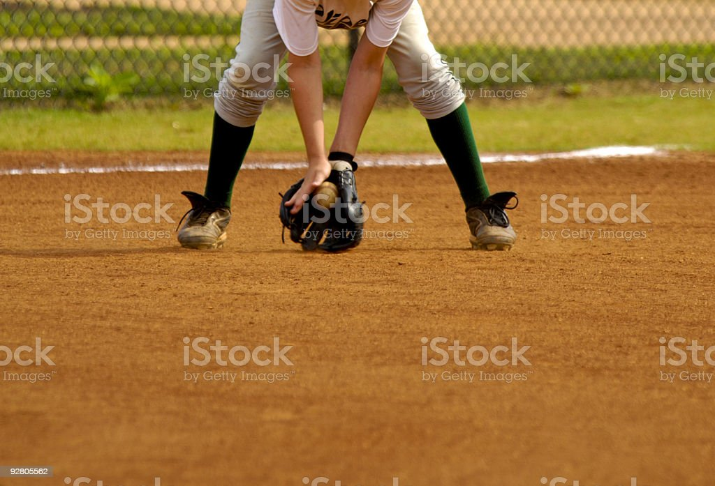Baseball Player Playing in Live Baseball Game while Fielding Baseball stock photo