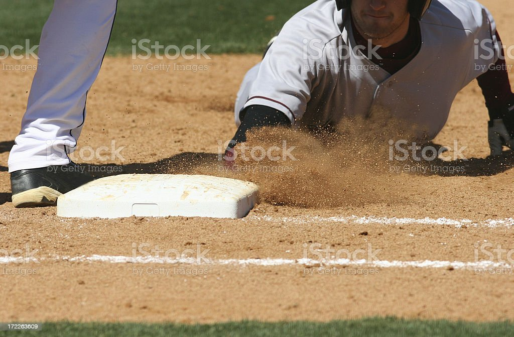 Baseball player sliding into base royalty-free stock photo