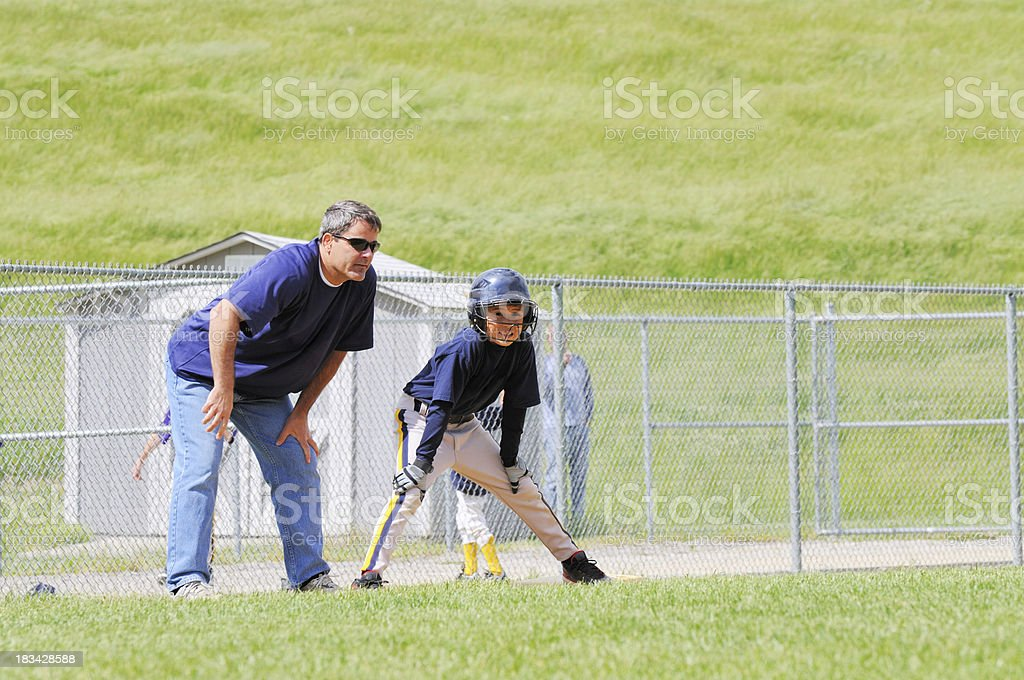 Baseball Player Son on Third Base with Coach Father stock photo
