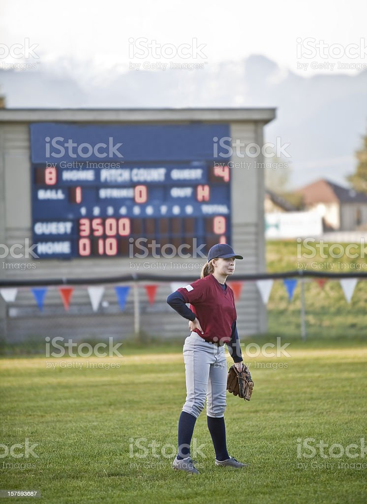 Baseball player Standing in Left Field with Scoreboard behind stock photo