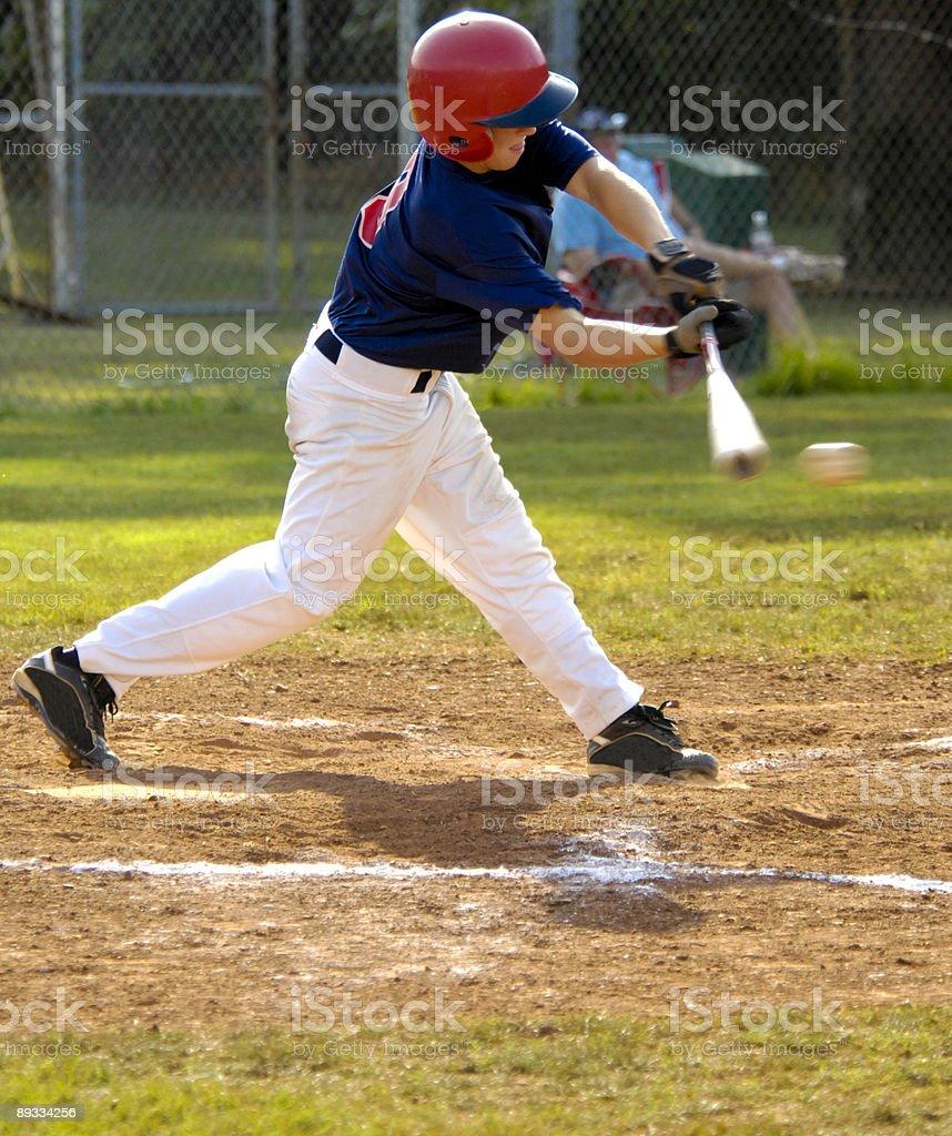 Baseball player swinging baseball bat at baseball at baseball game stock photo