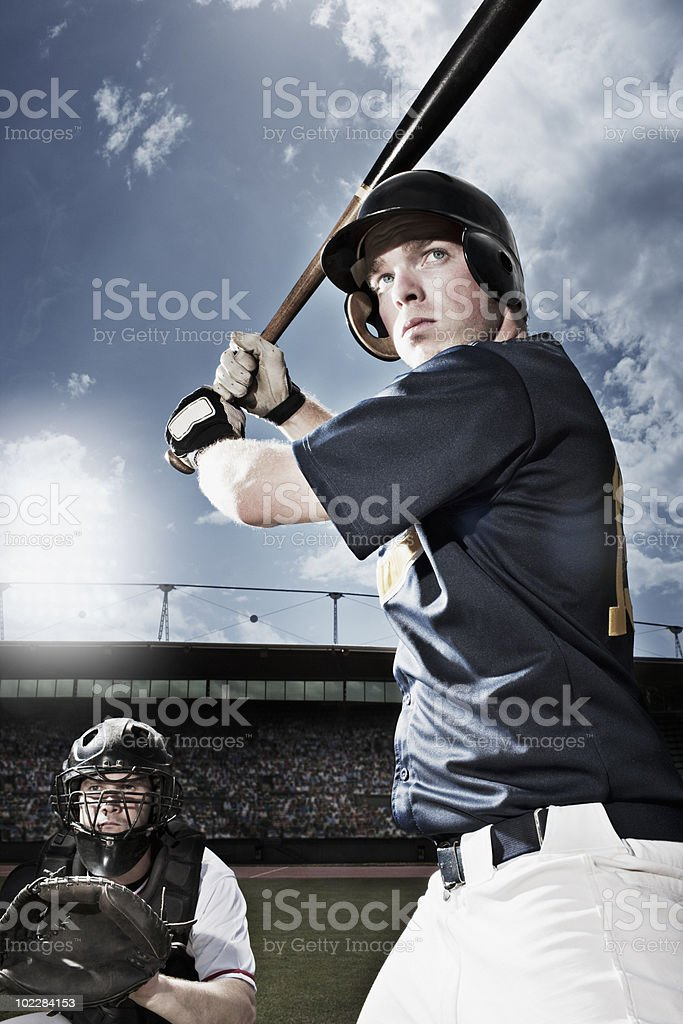 Baseball player swinging baseball bat stock photo