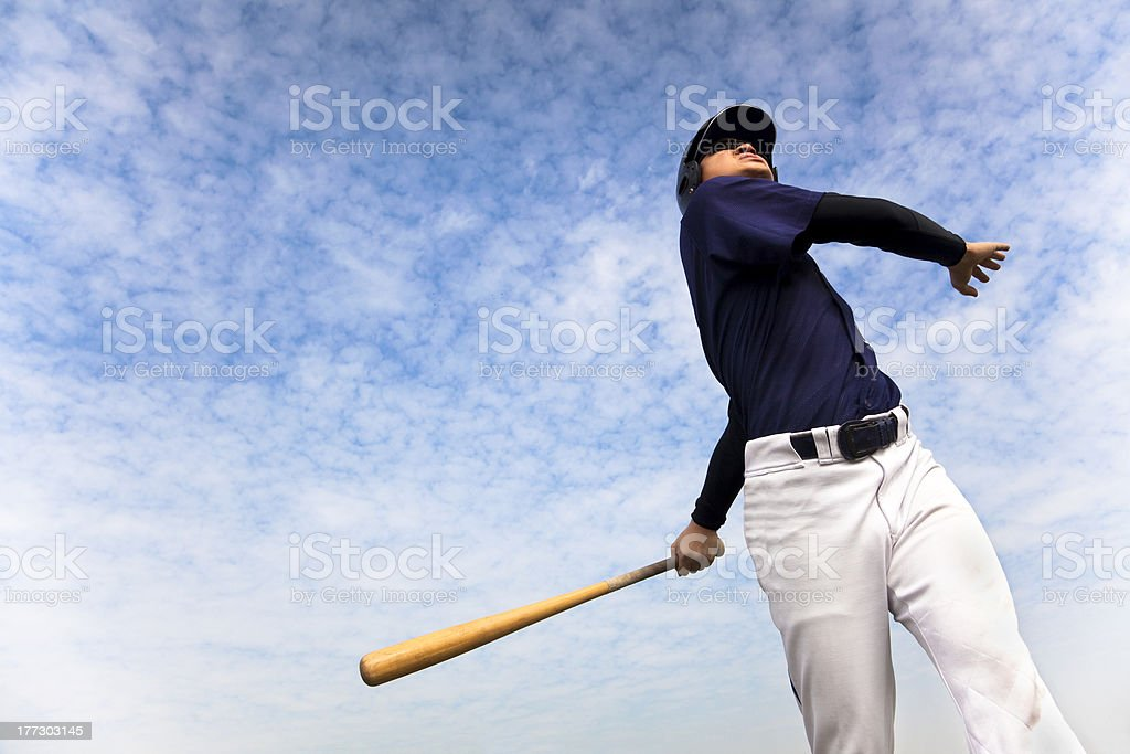 baseball player taking a swing with cloud background stock photo