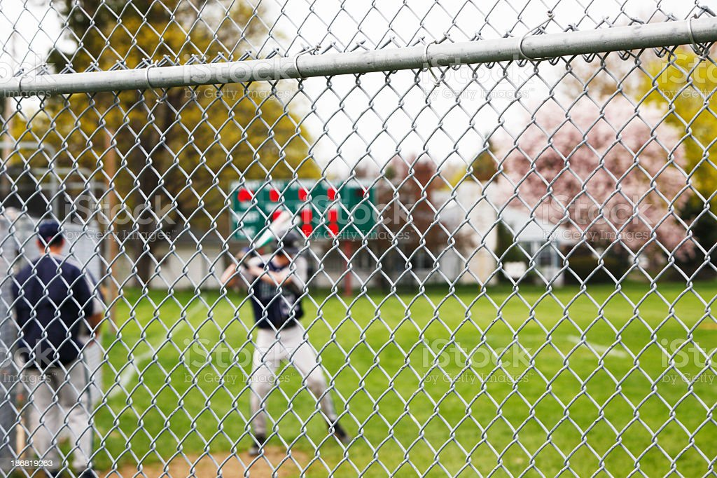 Baseball Player Taking Warmup Swings Beyond Chainlink Fence royalty-free stock photo