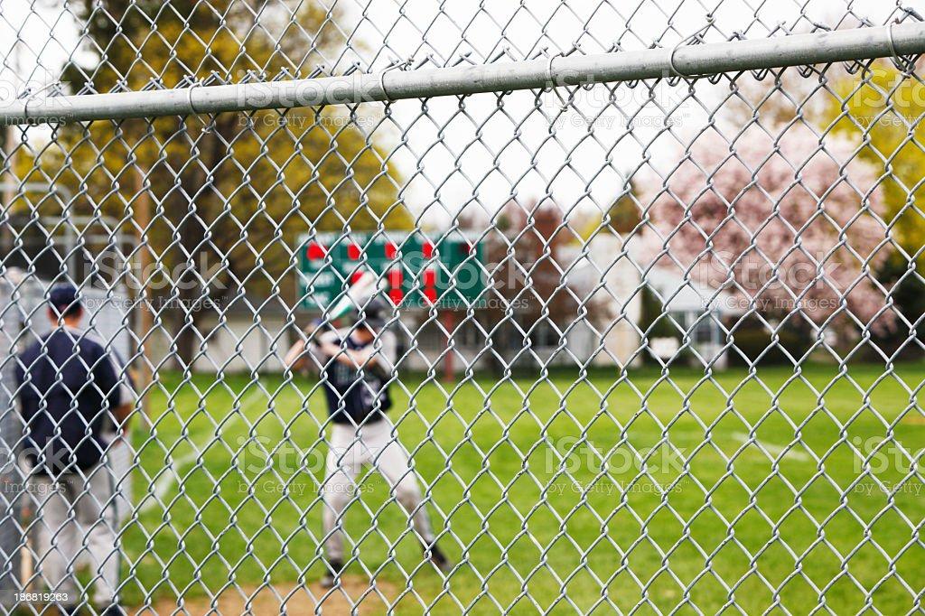 Baseball Player Taking Warmup Swings Beyond Chainlink Fence stock photo