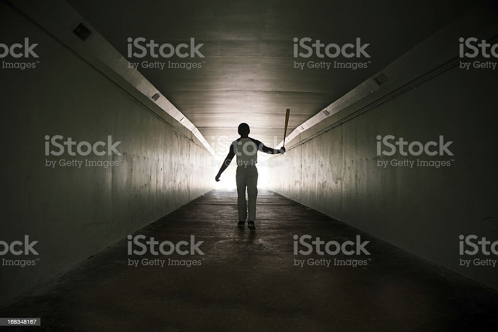 Baseball player walking out of stadium tunnel swinging bat  stock photo