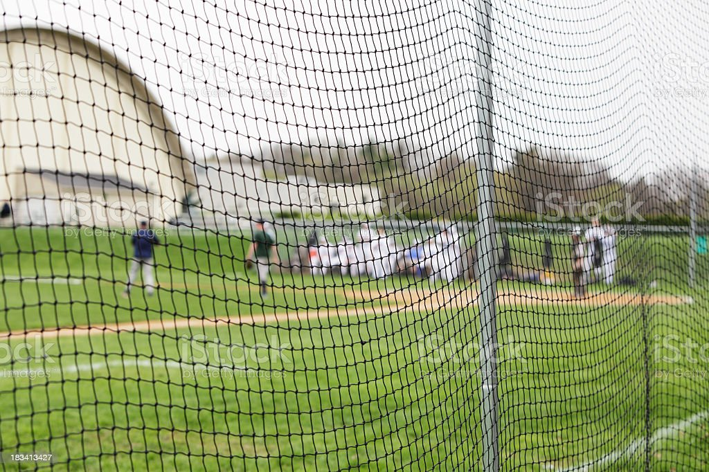 Baseball Players Behind Safety Net at High School Sports Game royalty-free stock photo