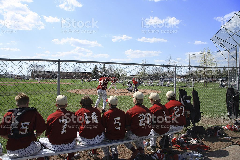 Baseball players on bench watching game through chain stock photo
