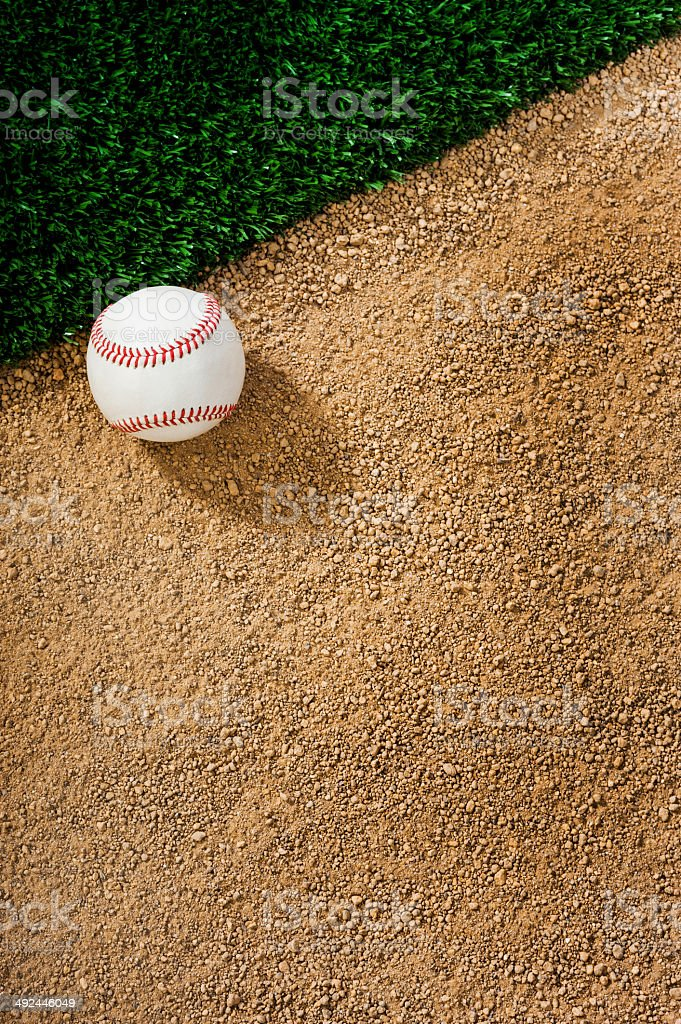 Baseball sitting on infield dirt next to grass stock photo