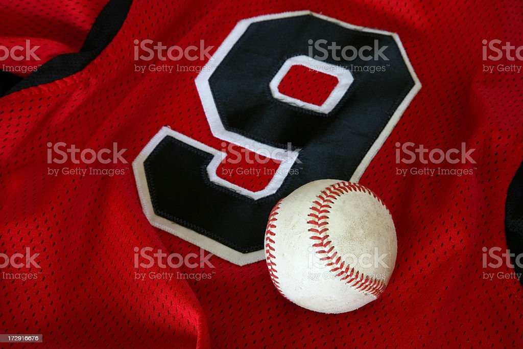 Baseball sitting on red sports jersey with black number 9 stock photo