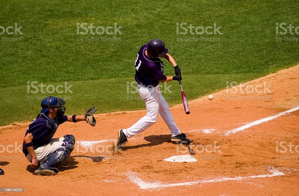 Baseball Swing as batter hits a pitched ball stock photo
